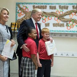 President Donald Trump poses for a photo with students of Saint Andrew Catholic School on Friday, March 3, 2017, during a tour of the school in Orlando, Florida. Also shown is U.S. Secretary of Education Betsy DeVos.
