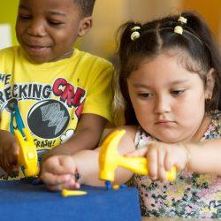 Preschool students practice hammering plastic nails into a foam pad in a sensory center.